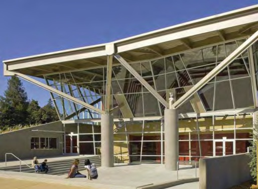 Steel struts surmounting massive concrete columns complement the oaks facing the lobby and support the exposed structure of the roof above the depressed entry courtyard sheltered by a branching structure designed to inspire spontaneous outdoor performances.
